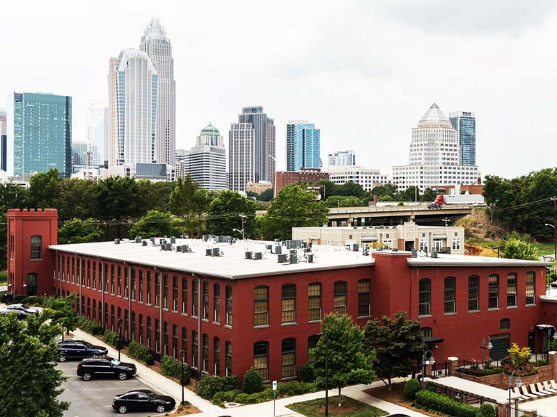 Alpha Mill Apartments showns from aerial view with the Charlotte skyline in the back