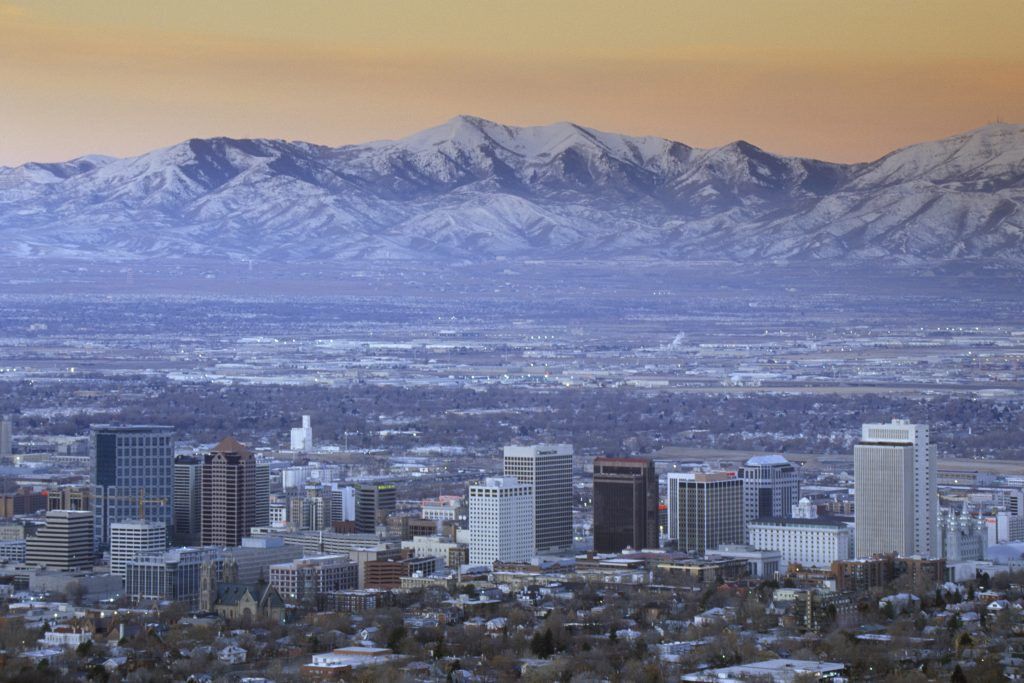 sunset view of salt lake city skyline with snow-capped mountains