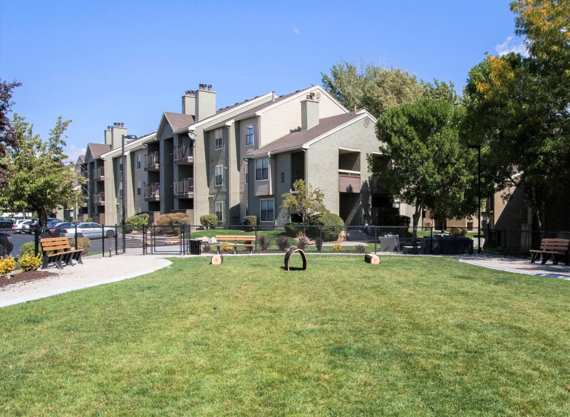 View of the Dog Park at Cottonwood Apartments, Showing Grass, Bench, Fenced-In Area, and Apartment Buildings in Background
