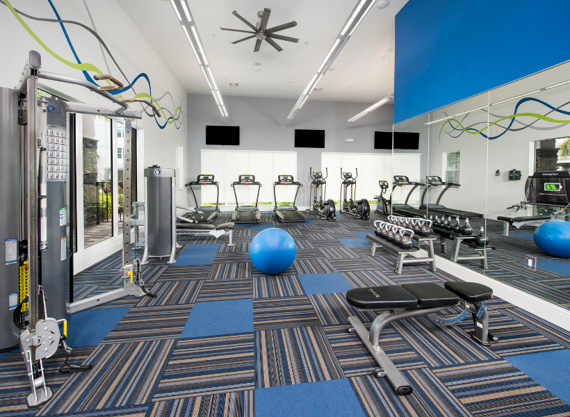 View of Cottonwood West Palm's Fitness Center, Showing Ceiling Fans, TVs, Cardio and Weight Machines.