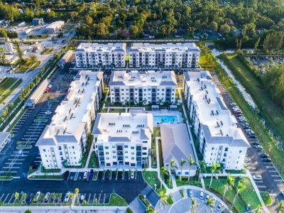 View of Apartment Exteriors, Showing Garages and Resident Parking, Screened-In Balconies, and Parking Lot at Cottonwood West Palm Apartments