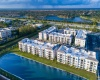 View of Overhead View of Property, Showing Adjacent Lake, Buildings, Surrounding Area, and Daytime View at Cottonwood West Palm Apartments
