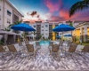 View of Pool Area, Showing Umbrellas and Lounge Seating, Sunset View, Buildings, and Cabanas at Cottonwood West Palm Apartments