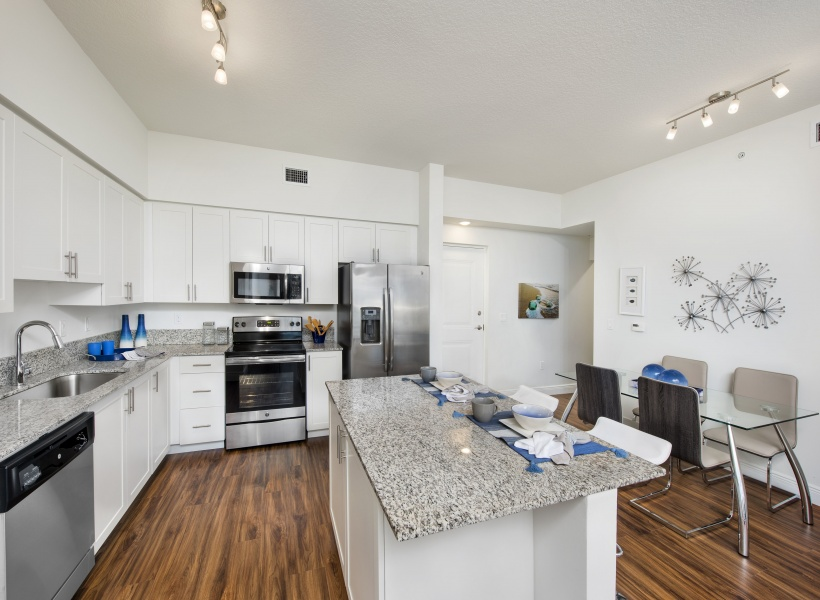 View of Apartment Kitchen, Showing Dining Table, Island Counter, Stainless Steel Appliances, and Granite Countertops at Cottonwood West Palm Apartments.