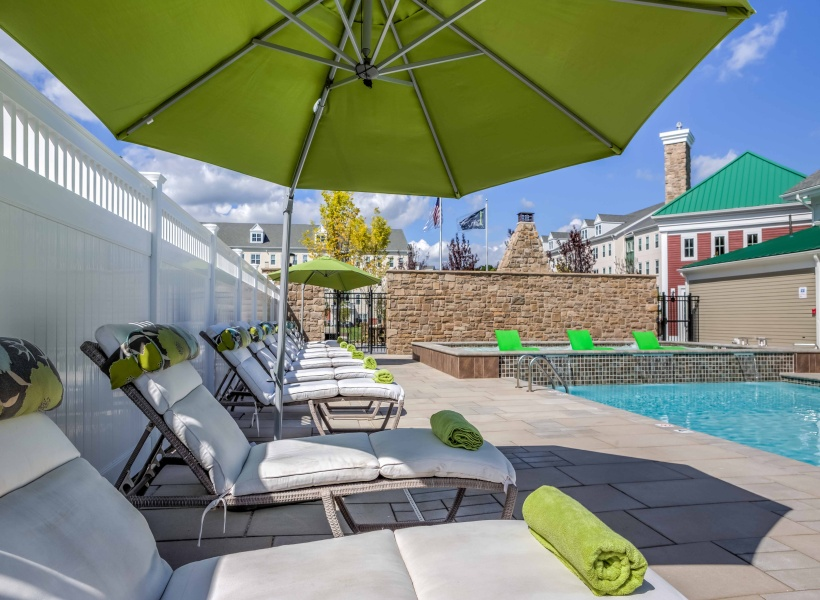 View of Pool Area, Showing Umbrella, Loungers, and Pooldeck at Cottonwood One Upland Apartments