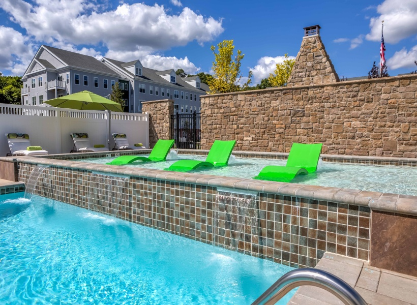 View of Pool Area, Showing Pool Chairs in Water, Blue Sky, and Shallow Area at Cottonwood One Upland Apartments