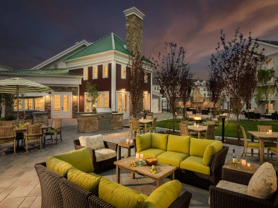 View of Outdoor Lounge Area, Showing Firepit, Sunset, and Leasing Office at Cottonwood One Upland Apartments