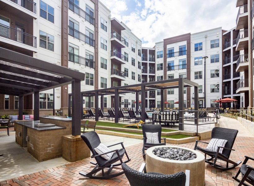 View of Firepit and Seating, with Cabanas and Adjacent Pool at Alexan Optimist Park Apartments
