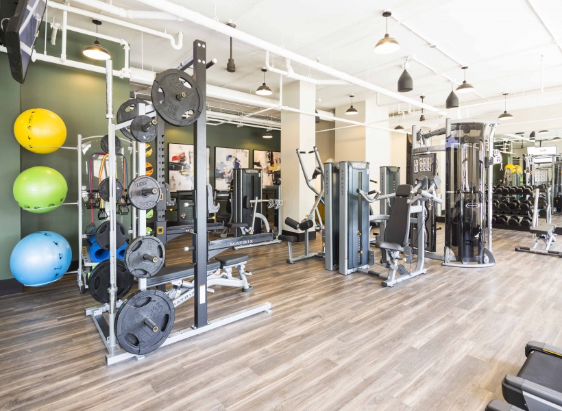 View of  Fitness Center, Rack Machines, and Weights at Alexan Optimist Park Apartments