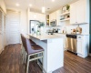 Kitchen with Island, White Custom Cabinets, and Stainless Appliances at Alexan Optimist Park Apartments