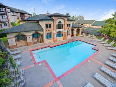 View of the Resort-Style Pool at Scott Mountain Apartments, Showing Aerial View With Loungers, and Exterior of Clubhouse