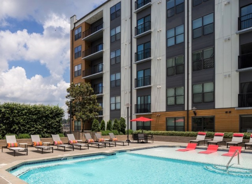 View of the Pool at Cottonwood Westside Apartments, Showing Loungers, Outdoor Furniture, Seating Areas, and Building Exterior