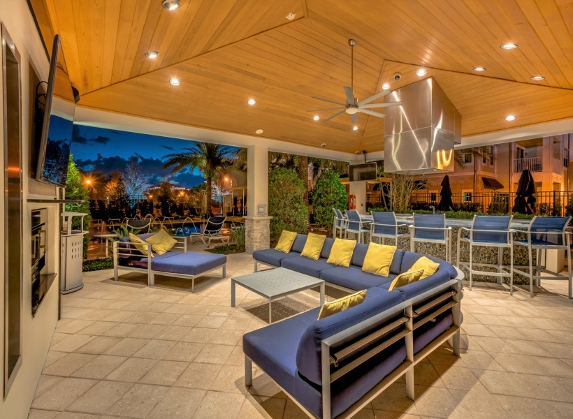 View of Pool Area, Showing Evening View of Pool, Loungers, Cabanas, and Palm Trees at The Marq Highland Park Apartments