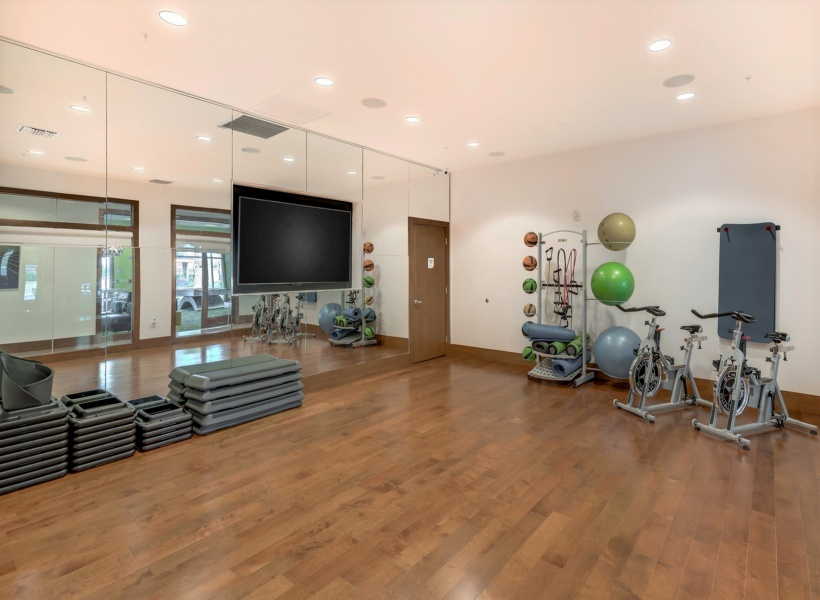 View of Fitness Center, Showing Exercise Machines, Free Weights, Benches, and TVs at The Marq Highland Park Apartments