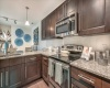 View of Kitchen, Showing Granite Countertop, Custom Cabinets, and Stainless Steel Appliances at The Marq Highland Park Apartments
