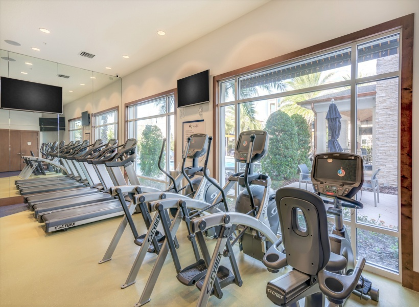 View of Fitness Center, Showing Treadmills, Ellipticals, Stationary Bicycle, and TV at The Marq Highland Park Apartments