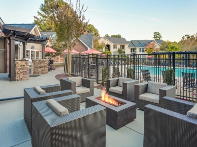 View of the Pool Area at Midtown Crossing Apartments, Showing Loungers, Table and Chairs, and Umbrellas