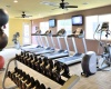 Camelot Apartments Fitness Center showing free weights, cardio machines, and tvs to watch while working out.