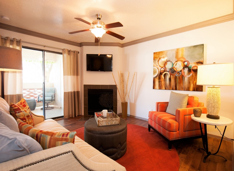 View of Furnished Living Room, Showing Fireplace, Ceiling Fan, and Door Leading to Private Patio at Pavilions Apartments