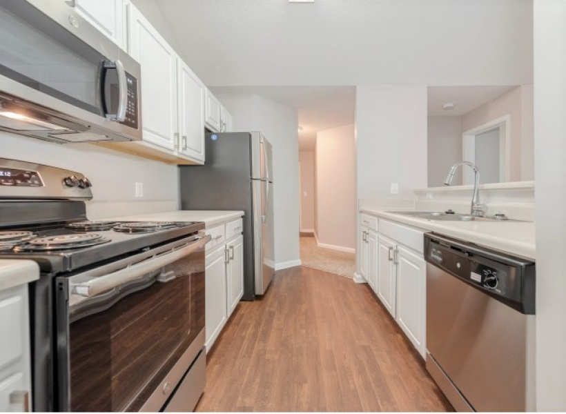 View of the Renovated Apartment Interior at Arbors at Fairview Apartments, Showing Galley Style Kitchen and Stainless Steel Appliances