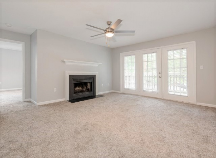 View of Renovated Apartment Interiors, Showing Living Room with Modern Paint and Doors to Patio at Plantations at Haywood Apartments