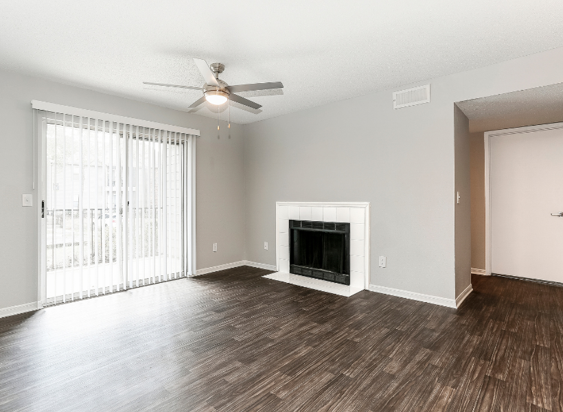 View of Renovated Apartment Interior, Showing Living Room With Fireplace, Ceiling Fan, and Window Doors to Patio at 1070 Main Apartments