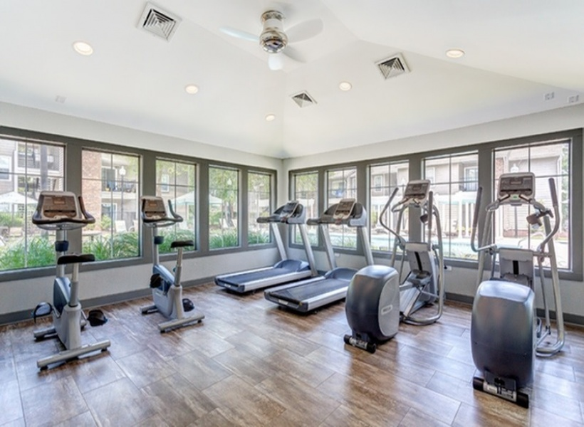 View of 1070 Mains Fitness Center, showing cardio machines with a view out to the pool area.