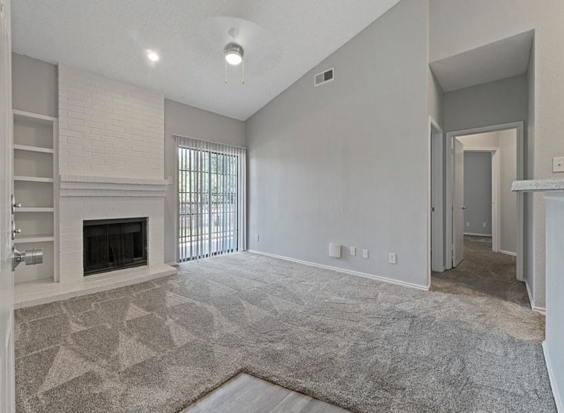 View of Renovated Apartment Interior; Showing Fireplace and View of Balcony at 4804 Haverwood Apartments