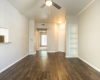 View of Renovated Apartment Interior Showing Living Room with Book Shelf, Plank Wood Flooring, and Ceiling Fan at Solara Apartments