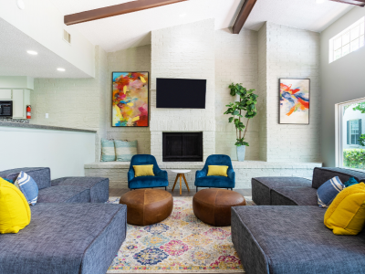 View of Clubhouse Showing Seating Areas, Art, Large House Plant, and a TV at Solara Apartments