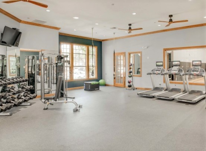 View of Fitness Studio, Showing Stationary Bikes, Wood Floor, TV, and Window View at Cottonwood Ridgeview Apartments