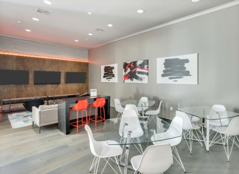 View of lounge area, showing flatscreen tv's, white chairs at glass tables, and art hung up, all at Cottonwood Ridgeview Apartments