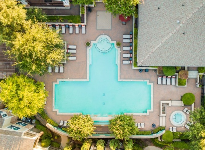 View of Pool Area, Showing Loungers, Tables with Umbrellas, Chairs, and Landscaping at Cottonwood Ridgeview Apartments