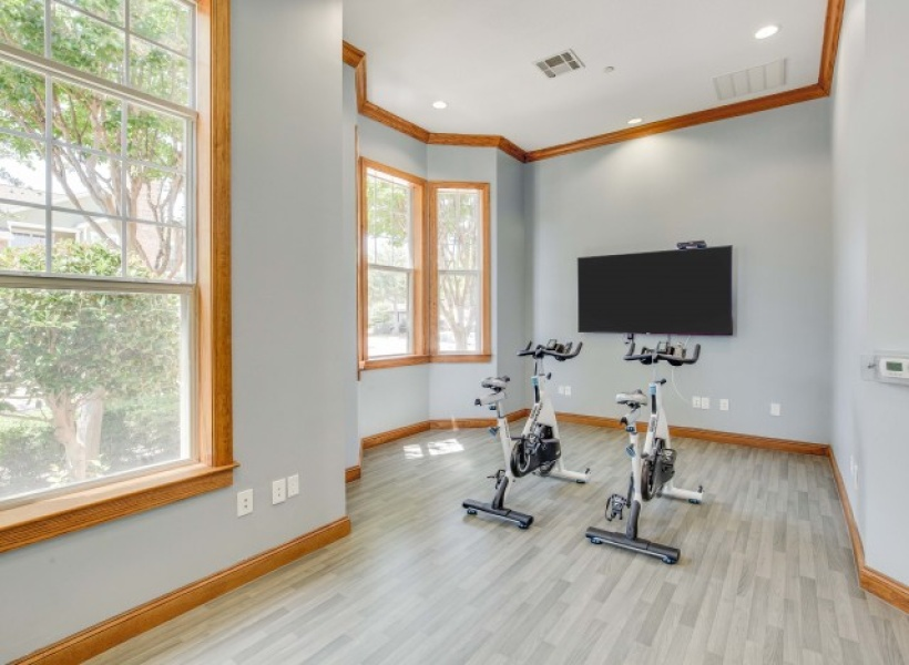 View of Cottonwood Ridgeview Apartments Spin room, showing two spin bikes facing a tv for video classes.