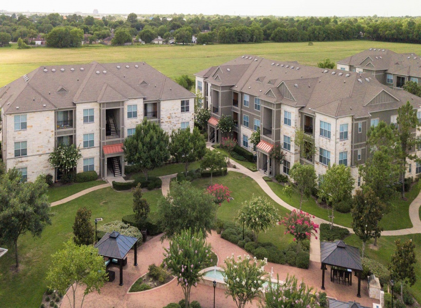 View of Building Exterior, Showing Aerial of Community, Pool, Green Space, and Parking at Retreat at Stafford Apartments