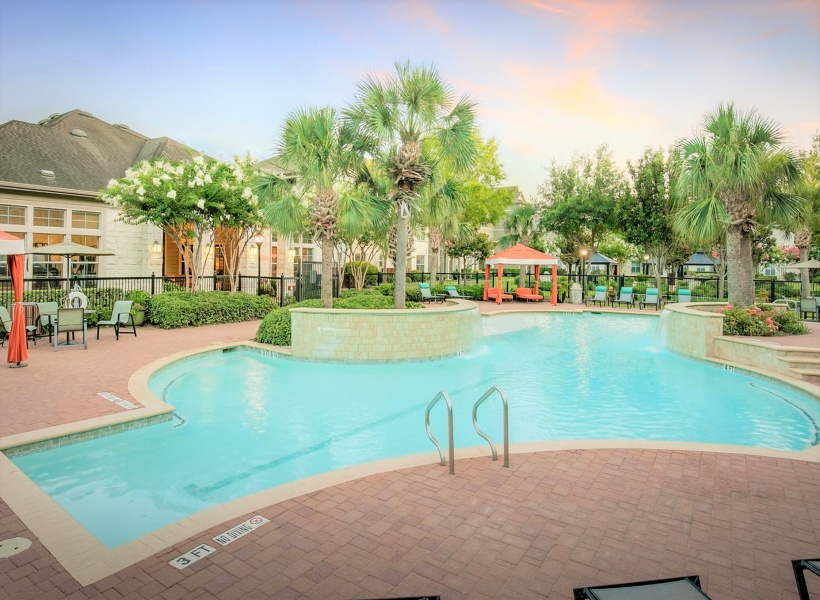 View of Poolside Cabanas, Showing Oversized Lounge Chairs, Seating and Pool at Dusk at Retreat at Stafford Apartments