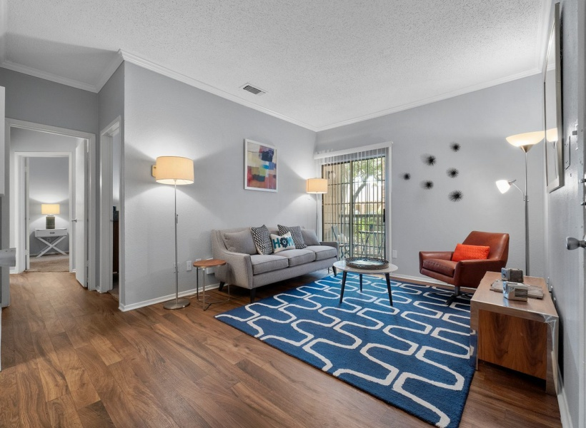 View of Renovated Apartment Interior, Showing Living Room with Plank Wood Flooring at The Oaks of North Dallas Apartments