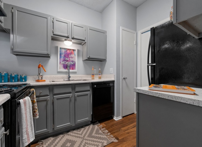 View of Renovated Apartment Interior, Showing Kitchen with Plank Wood Flooring and Gas Appliances at The Oaks of North Dallas Apartments