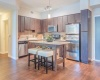 View of Kitchen, Showing Island, Stainless Steel Appliances, and Plank Wood Flooring at Cottonwood Bayview Apartments