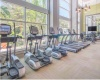 View of Fitness Center, Showing Bench, Cardio Machines, Window View, and TV at Cottonwood Bayview Apartments