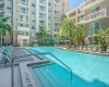 View of Pool, Showing Loungers, Pergola, and Apartment Building in Background at Cottonwood Bayview Apartments