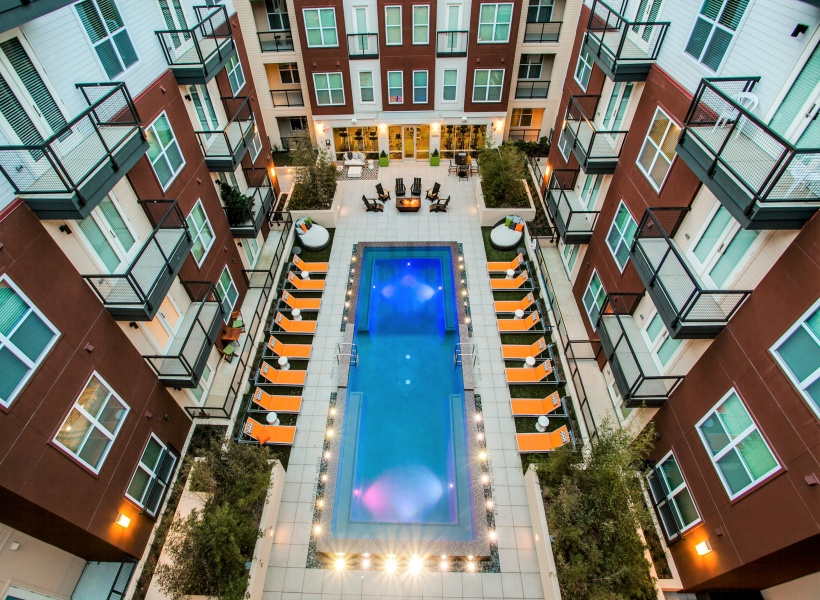 View of Pool Area, Showing Aerial Image of Loungers, Fire Pit, Patios, and Balconies at Routh Street Flats Apartments