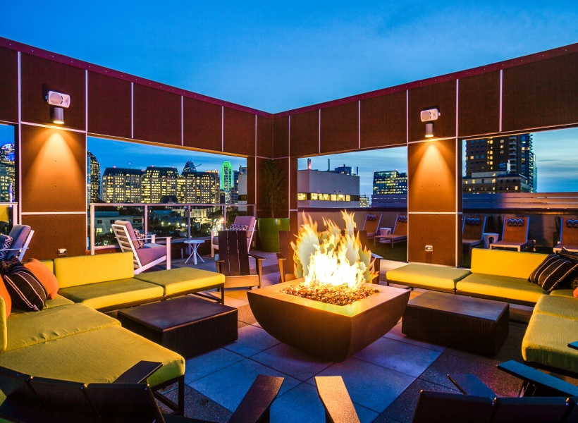 View of Rooftop Lounge, Showing Fire Pit, Chairs, and Outdoor Furniture at Routh Street Flats Apartments