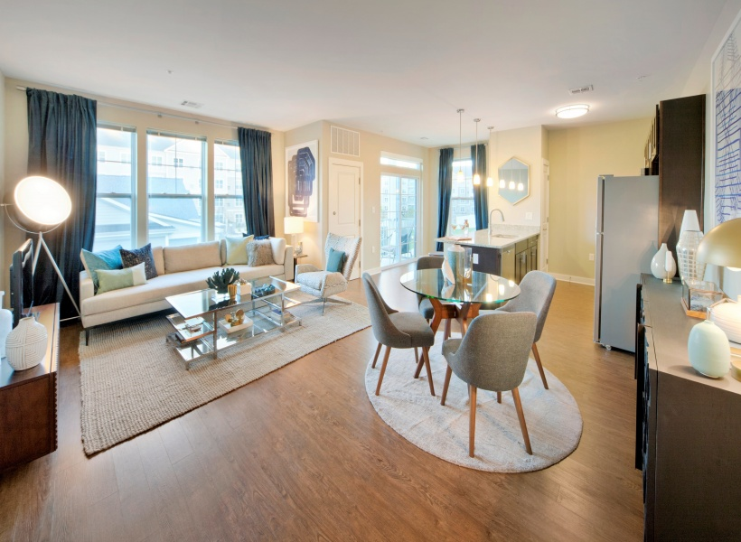 View of Furnished Living Room, Showing Dining Area, Kitchen, and Plank Flooring at Parc Westborough Apartments