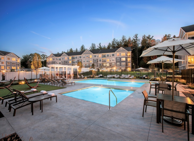 View of Pool Area, Showing Pergola, Picnic Tables, Pools, and Adjacent Resident Lounge at Parc Westborough Apartments